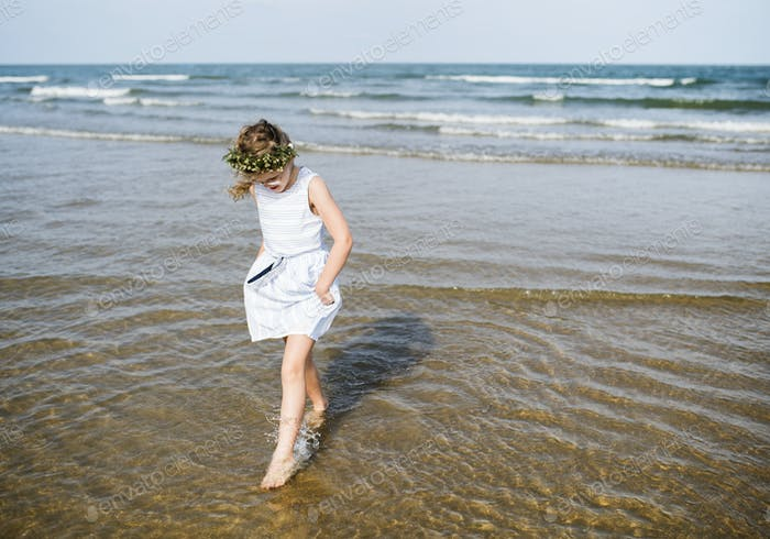 Little girl walking in the water