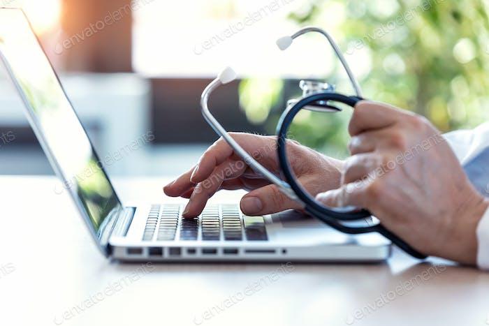Hände des unkenntlich Arztes schreiben auf einem Computer.