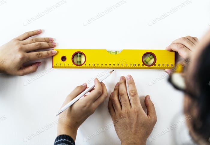 Asian couple measuring the wall