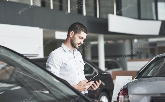Молодые продавцы с папкой для продажи нового автомобиля