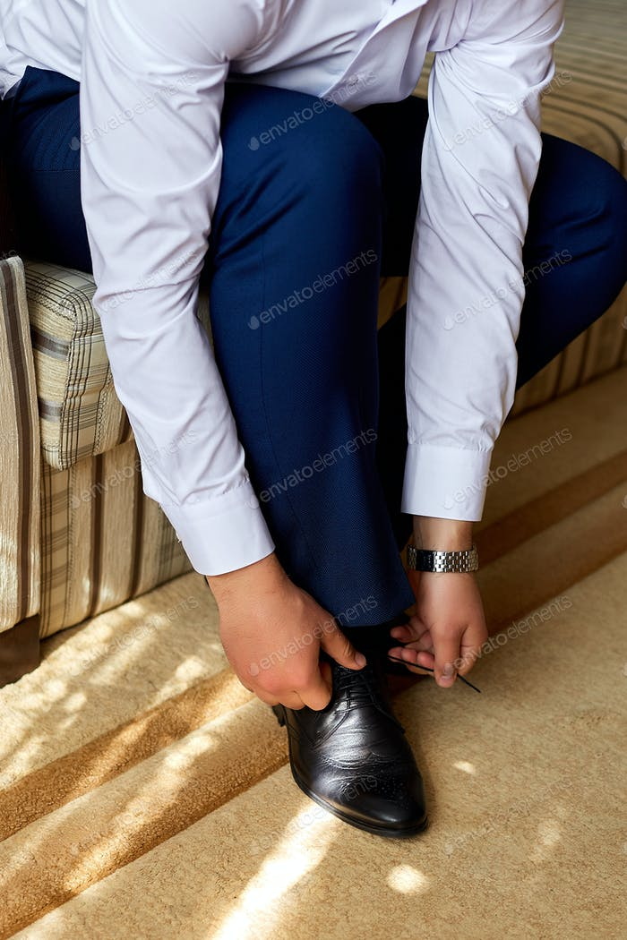Elegant young fashion man dressing up for wedding celebration.