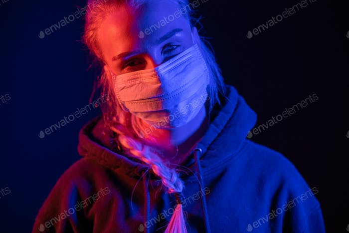 Exhausted or sick woman in protective face mask with multi colored lights