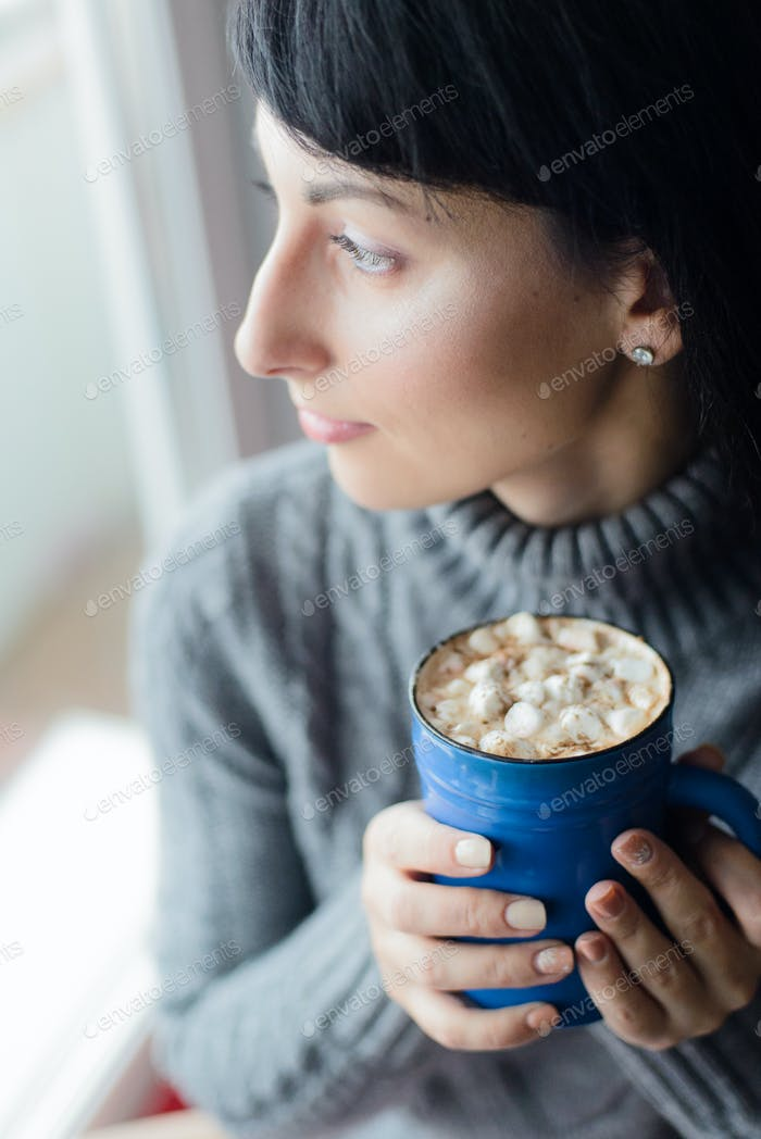 woman on windowsill with cocoa looking through window