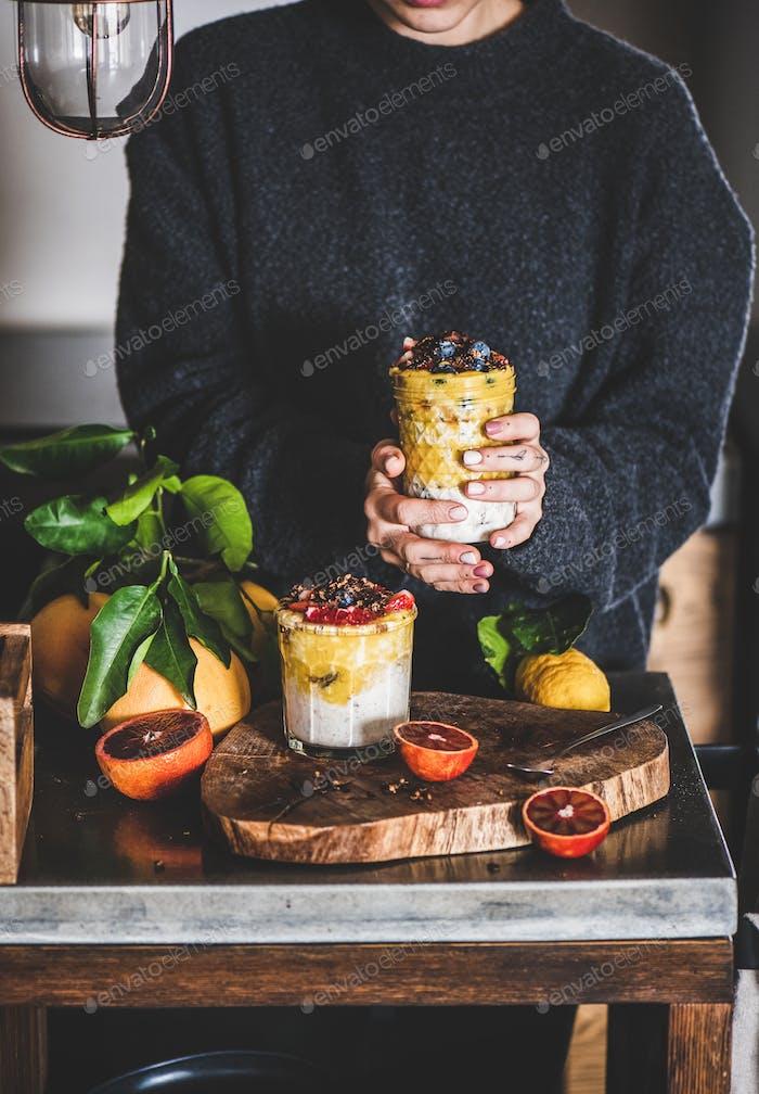 Frau hält Glas Müsli mit Mango Smoothie, Müsli, Beeren