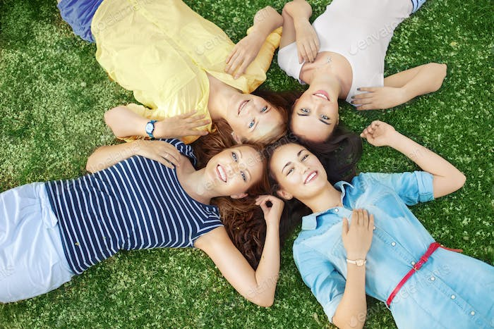 Four girlfriends lying down on the ground and looking up on summer day