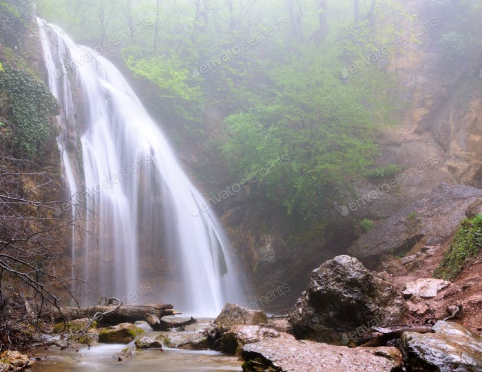 Waterfall flows in mountain forest