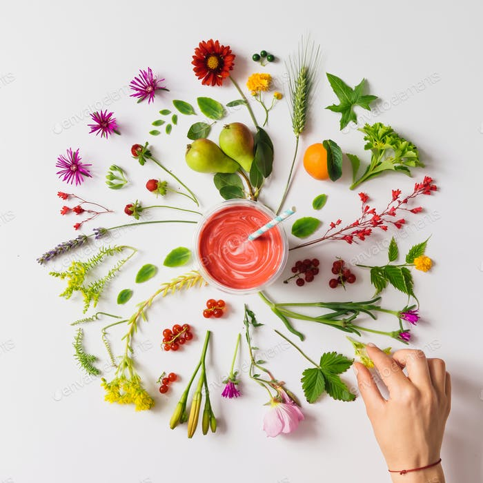 Various natural things neatly arranged in circle with smoothie