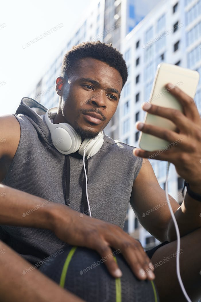 African Man Using Smartphone Outdoors