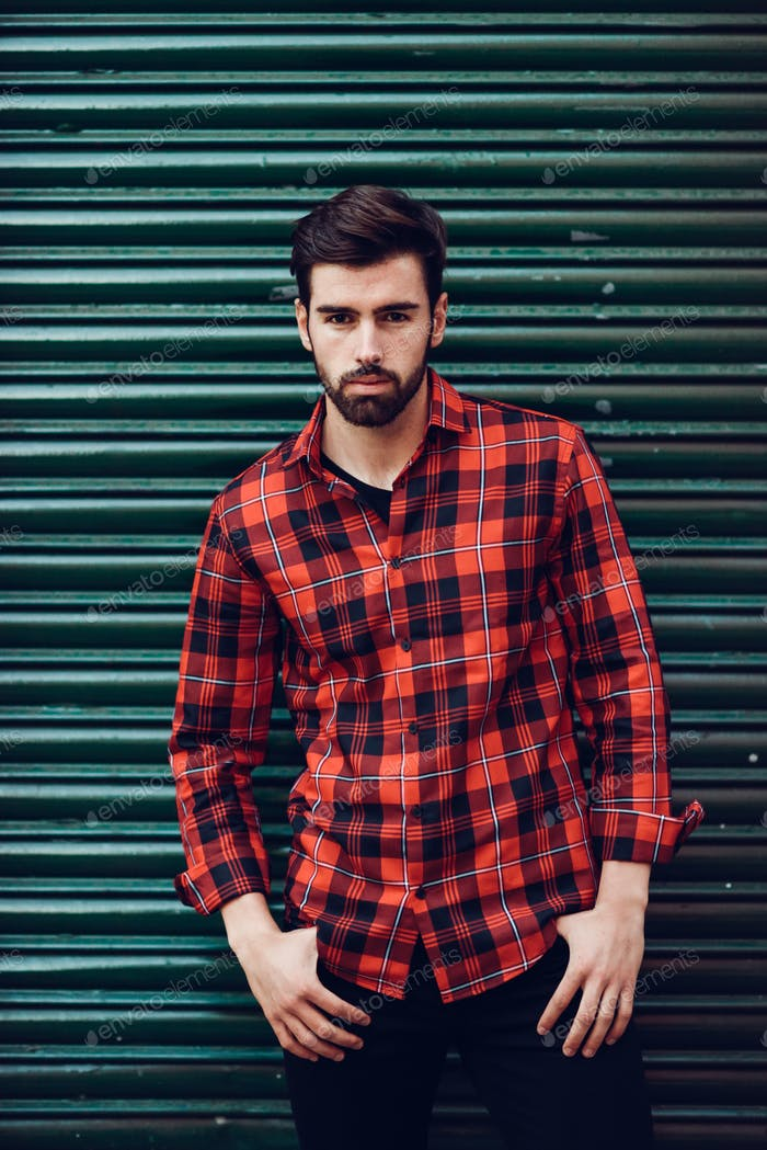 Young bearded man, model of fashion, wearing a plaid shirt with