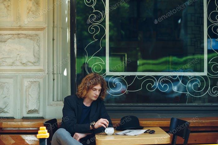 Portrait interesting reddish man mixing coffee outdoors