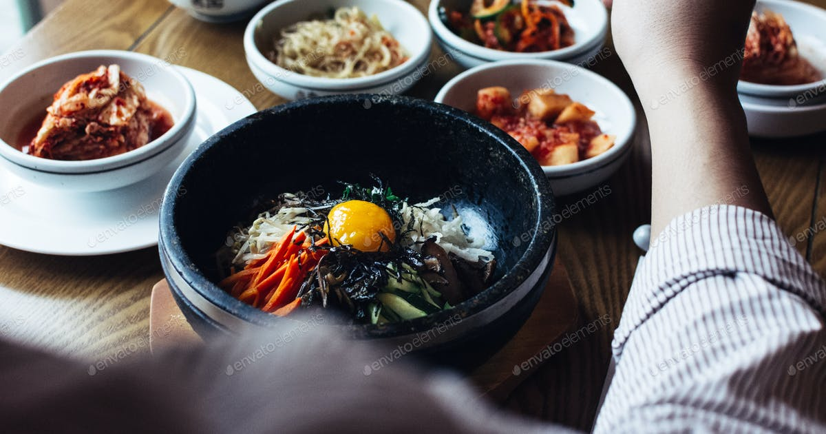 Feasting On Bibimbap Kimchi And Other Traditional Korean Food Photo By Kapusnak On Envato Elements