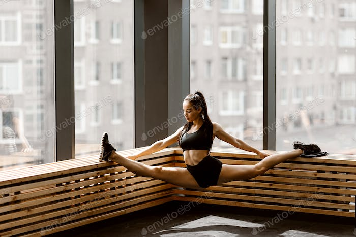 Beautiful slander girl dressed in black sports top and shorts is doing stretching on a wooden window