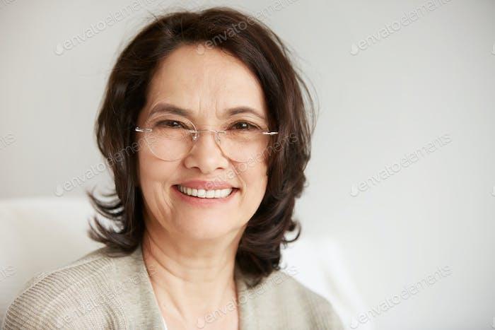 Attraktive Brünette Frau mittleren Alters mit einem schönen Lächeln vor dem Hintergrund der Apartments