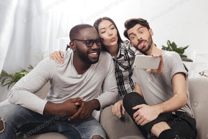 Three young friends sitting on sofa at home and taking cute selfies on phone together