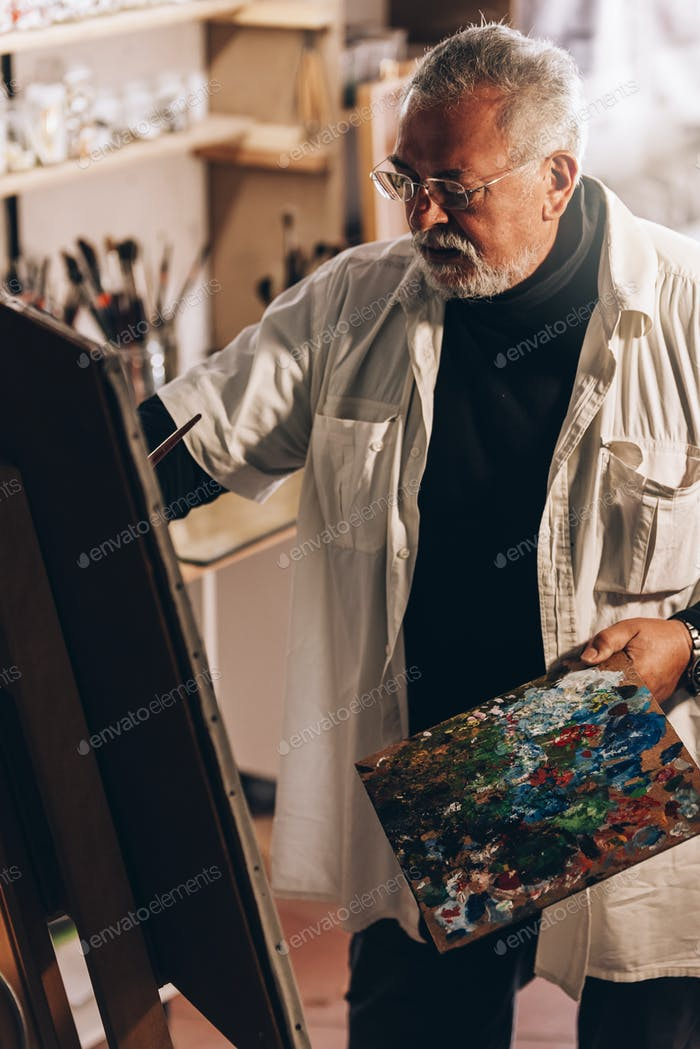 Old man artist painting oils in his studio.