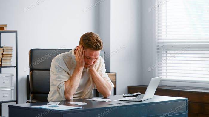 Young male financial director reads bank reports sitting at grey table