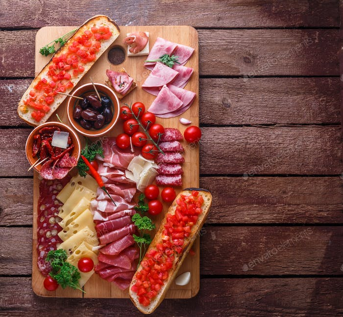 Meat and cheese appetizer set for red wine on rustic background, flatlay, copy space.