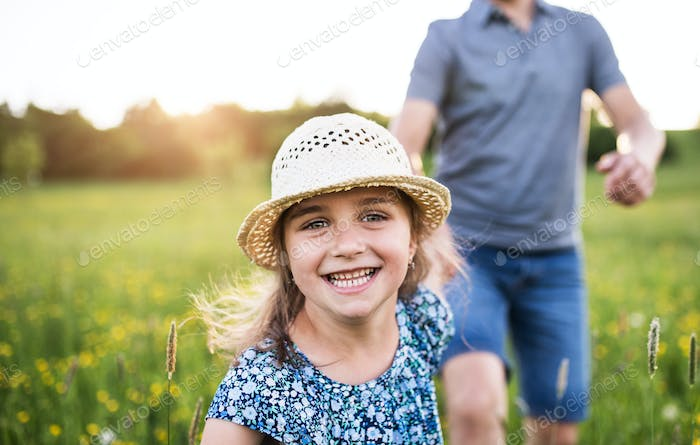 Father with a small daughter running in spring nature.