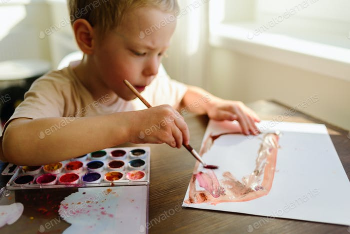 Child drawing in watercolor very enthusiastically
