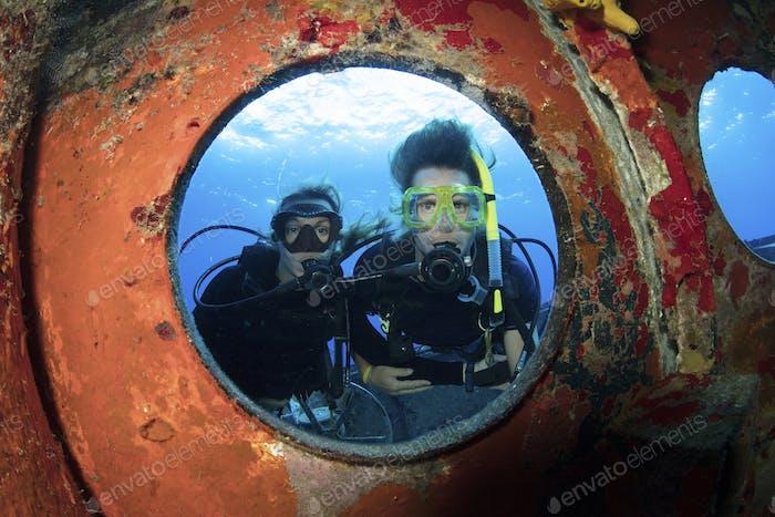 Los buzos miran a través de un ojo de buey en el casco de un naufragio