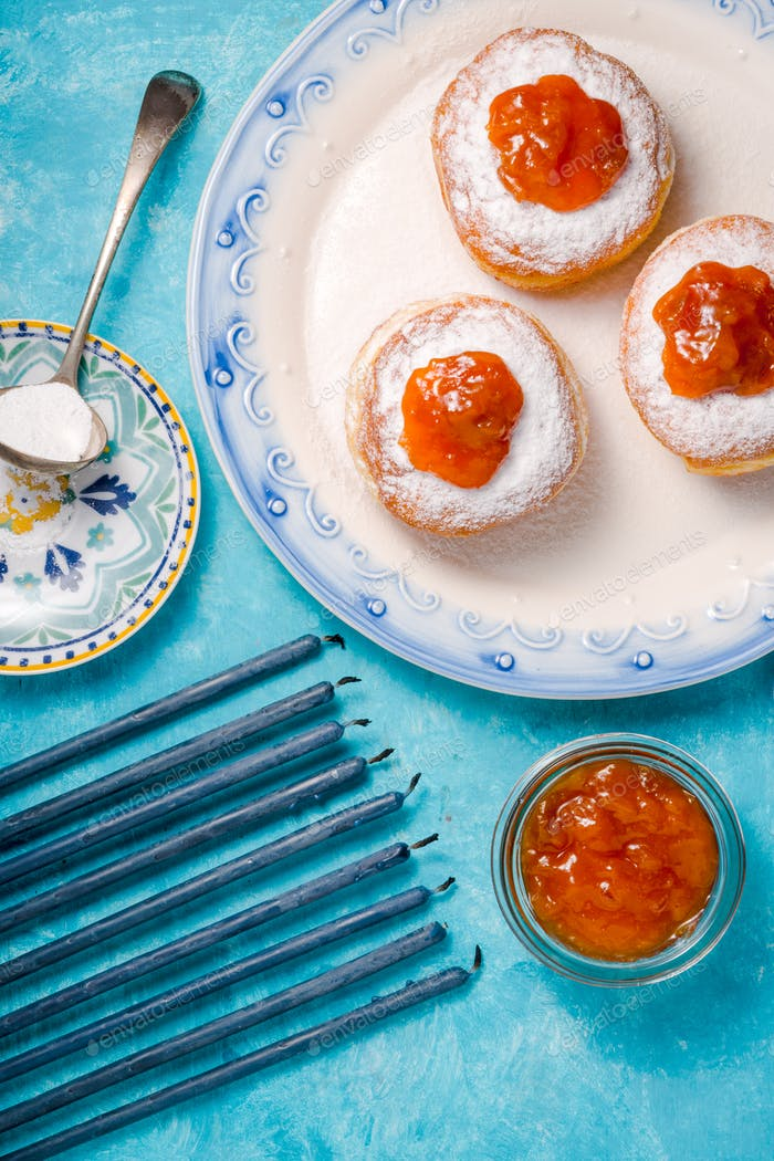 Blue candles, a plate with donuts and jam on a turquoise table close-up