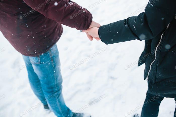 Пара держатся за руки