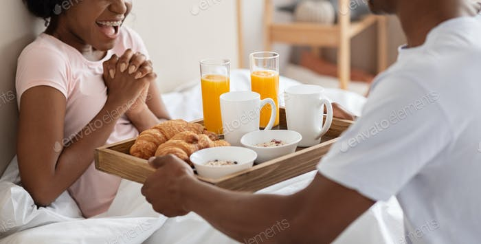 Cropped of african man bringing breakfast in bed for woman