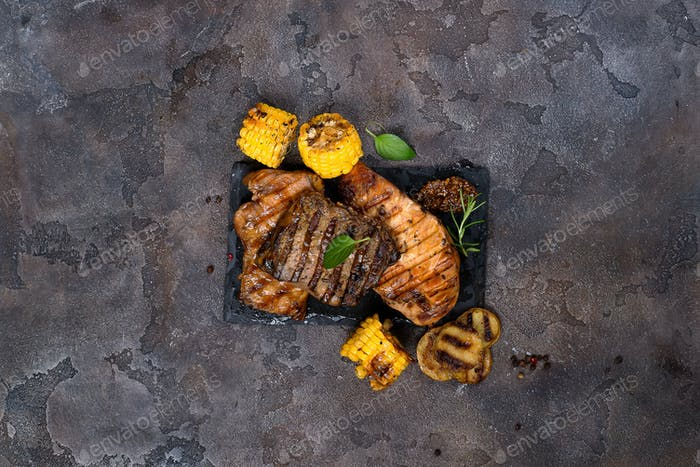 Fresh three types of grilled steak on slate plate with herbs and grilled potatoes