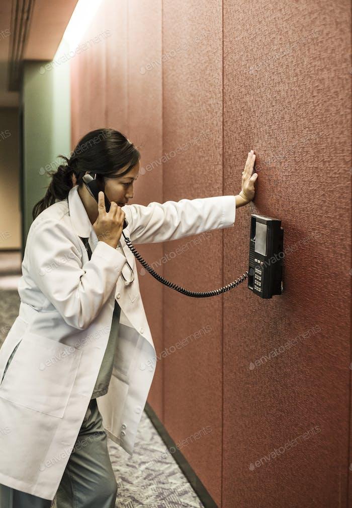 Asiasn woman doctor on a phone in a hospital lobby.