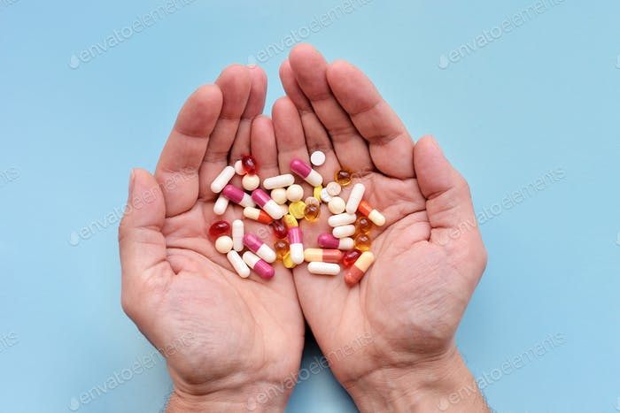 A man is holding a different pills in both his hands on blue background. Top view