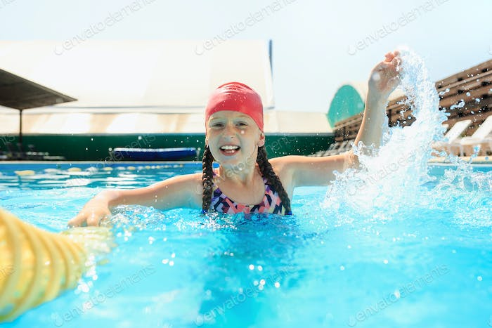 The portrait of happy smiling beautiful teen girl at the pool