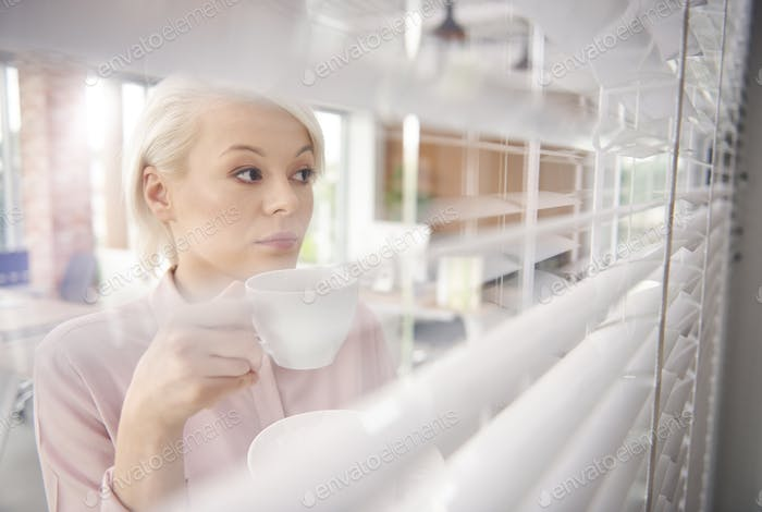 Businesswoman with coffee looking through blinds