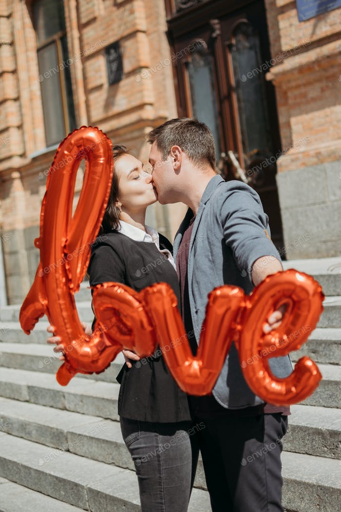 Valentines day celebration and dating concept. Happy loving couple with red Love Balloons in the