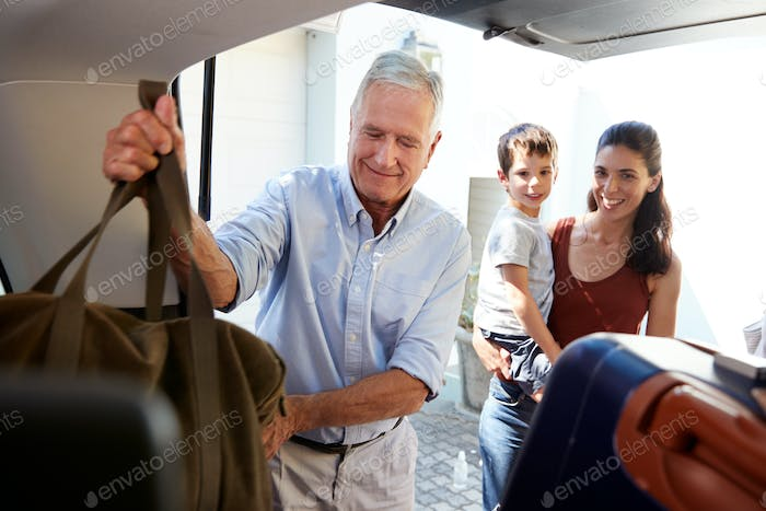 Senior white man packing car boot with holiday luggage, watched by his adult daughter and grandson