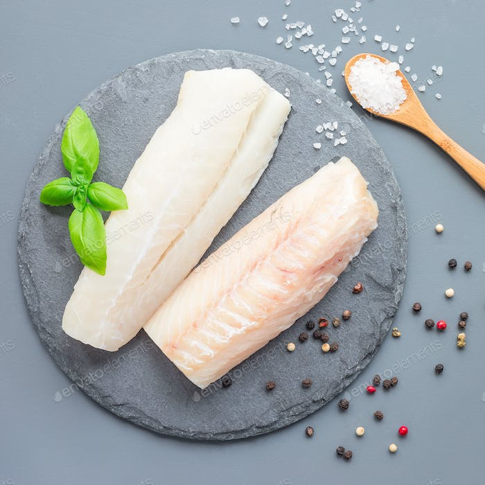 Fresh raw cod fillet with spices, pepper, salt, basil on a stone