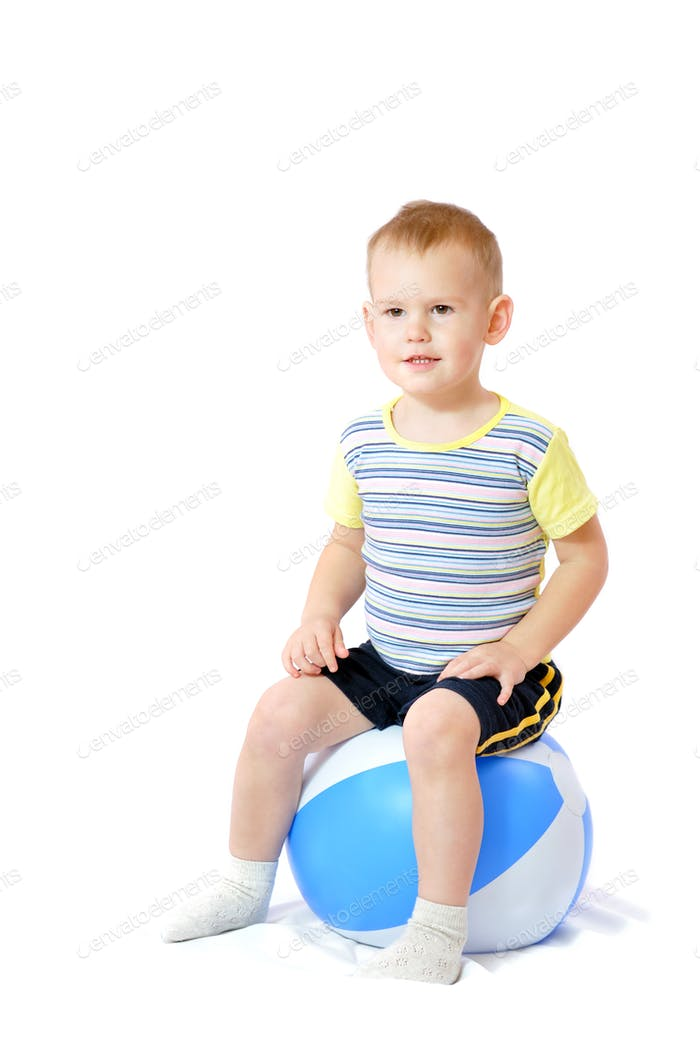 Little boy sits on inflatable ball