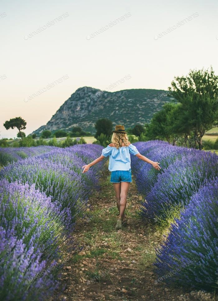 Young blond woman traveller walking in lavender field, Isparta, Turkey