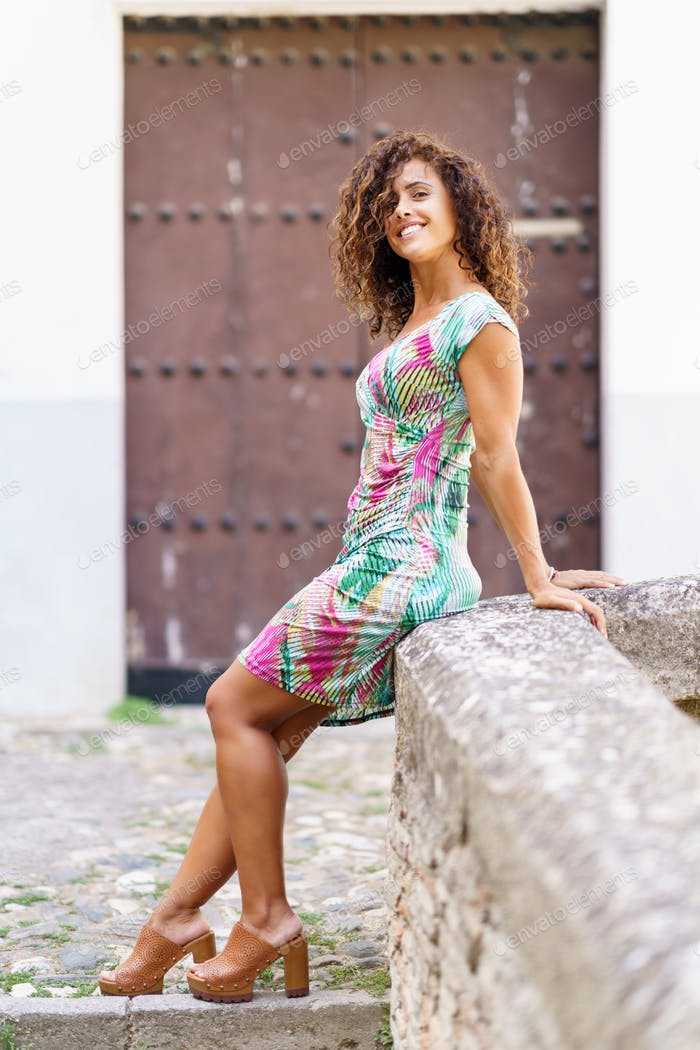 Beautiful brunette middle-aged woman wearing spring colorful dress outdoors