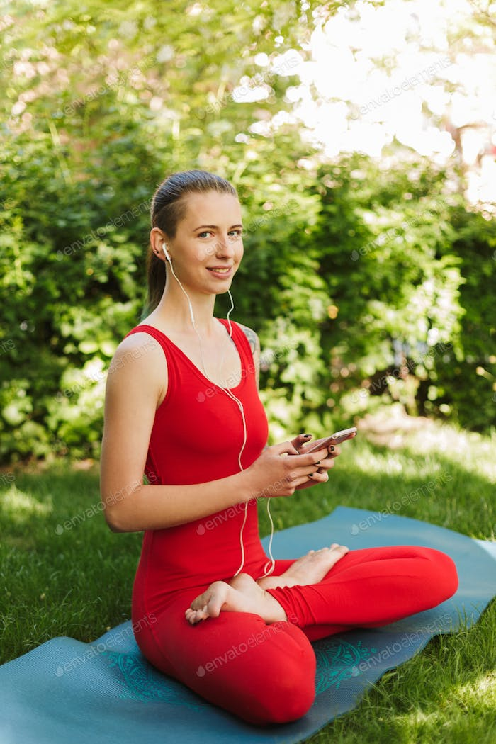 Young smiling woman in red jumpsuit sitting in lotus pose on yoga mat in park