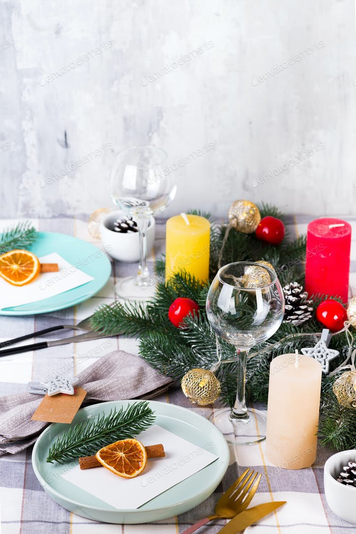 estive Christmas and New Year table setting with dry orange and cinnamon on a gray textile. Dining