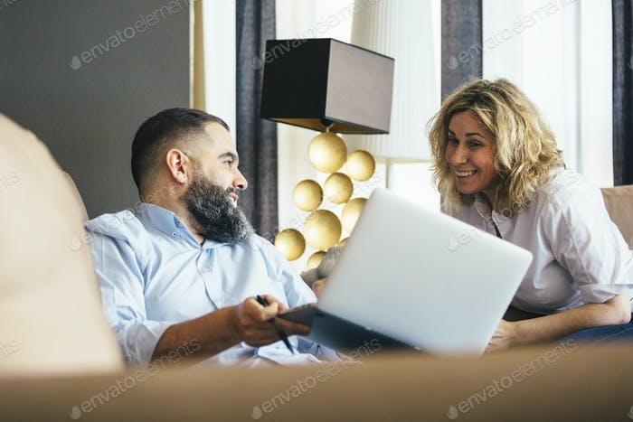 Colleagues smiling on sofa with laptop