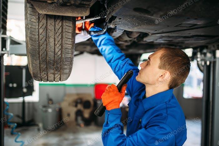 Mechaniker mit Lampe überprüft die Fahrzeugaufhängung
