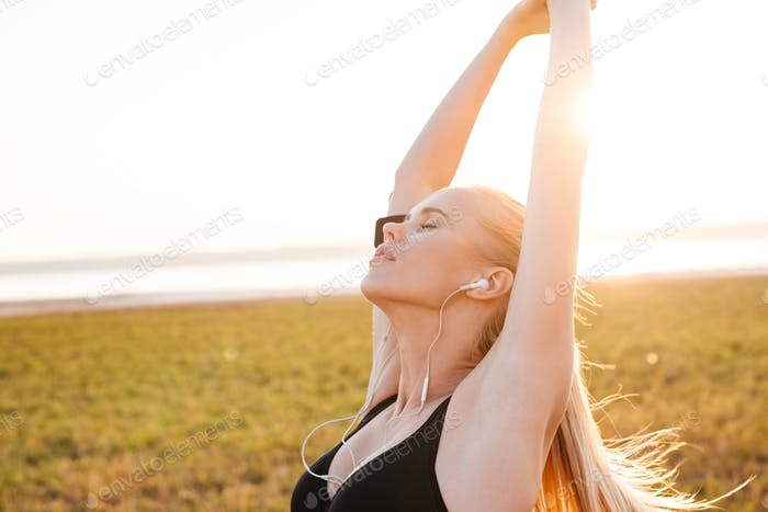 Young fitness woman with eyes closed doing stretching exercises