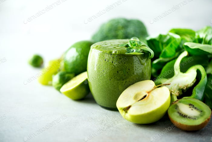 Glass with green health smoothie, kale leaves, lime, apple, kiwi, grapes, banana, avocado, lettuce