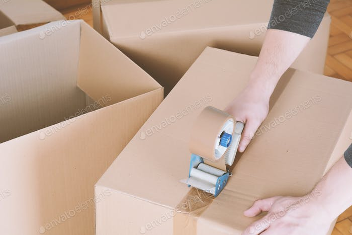 Man sealing a shipping cardboard box