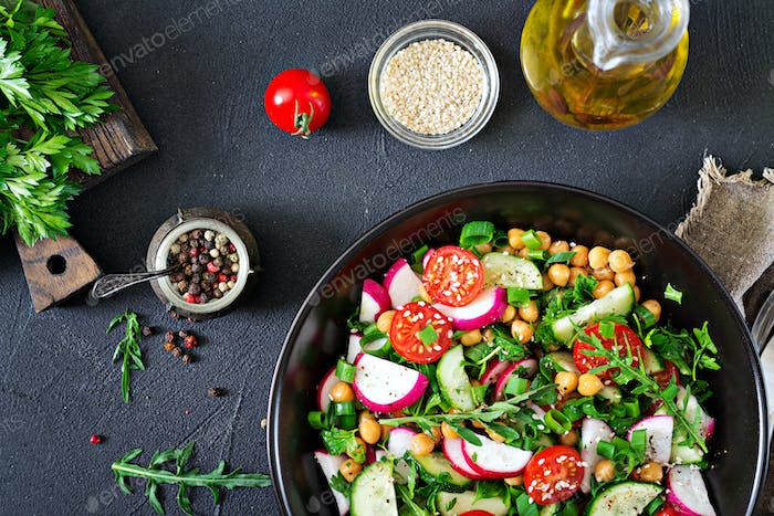 Salad of chickpeas, tomatoes, cucumbers, radish and greens.