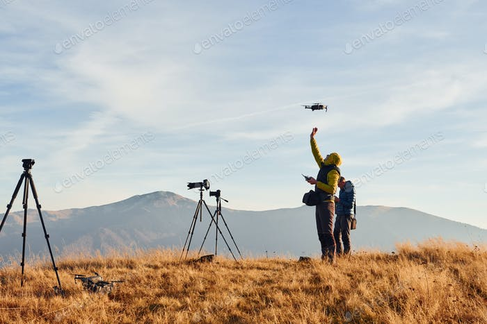 Male photographers standing and working at majestic landscape of autumn trees and mountains