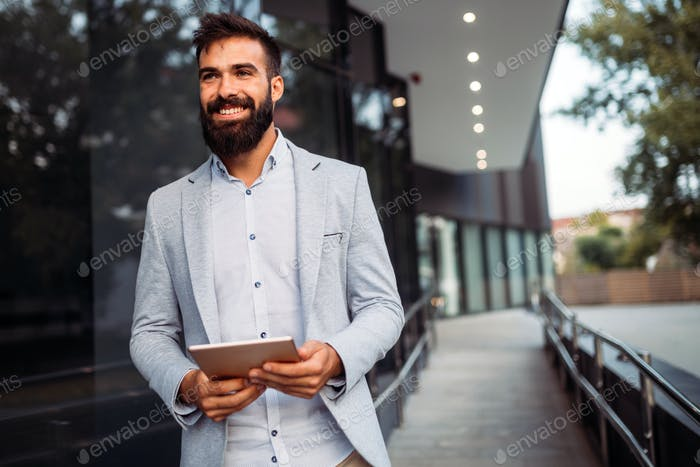 Portrait of young businessman in front of company
