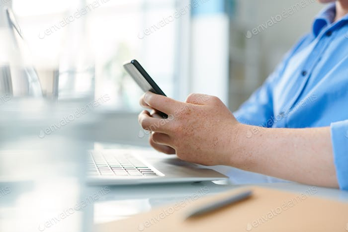 Young contemporary student or employee holding smartphone over workplace