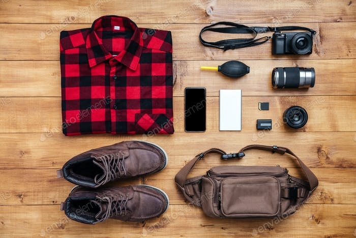 Travel concept boots, shirt, camera, mobilephone, bag, mp3,